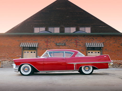 AUT 21 RK2599 01 © Kimball Stock 1957 Cadillac Coupe de Ville Red Profile View On Pavement By Building