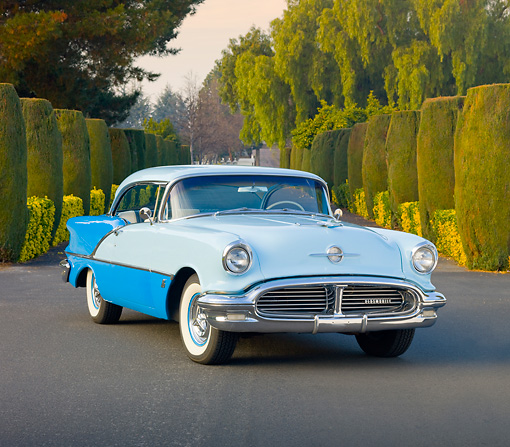 AUT 21 RK2615 01 © Kimball Stock 1956 Oldsmobile Super 88 Blue On Road In Front Of Trees