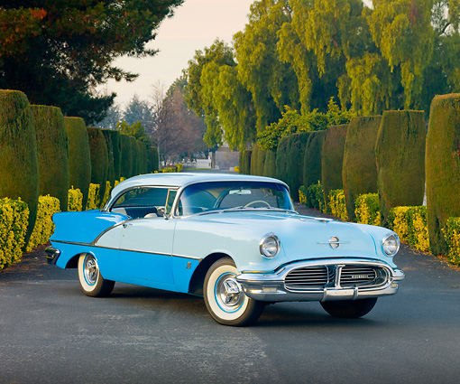 AUT 21 RK2616 01 © Kimball Stock 1956 Oldsmobile Super 88 Blue On Road In Front Of Trees