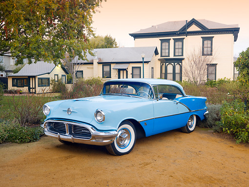 AUT 21 RK2618 01 © Kimball Stock 1956 Oldsmobile Super 88 Blue On Dirt In Front Of A House