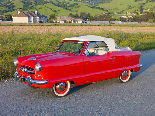 AUT 21 RK2640 01 © Kimball Stock 1955 Nash Metropolitan Convertible Red 3/4 Side View On Pavement By Field And Houses