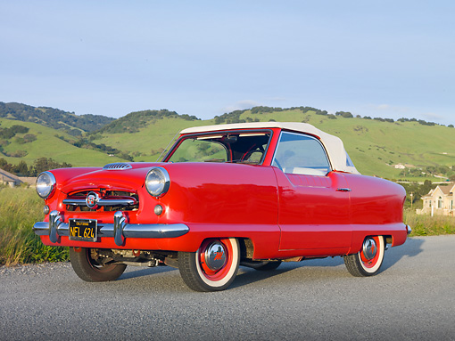 AUT 21 RK2641 01 © Kimball Stock 1955 Nash Metropolitan Convertible Red 3/4 Side View On Pavement By Grassy Hills