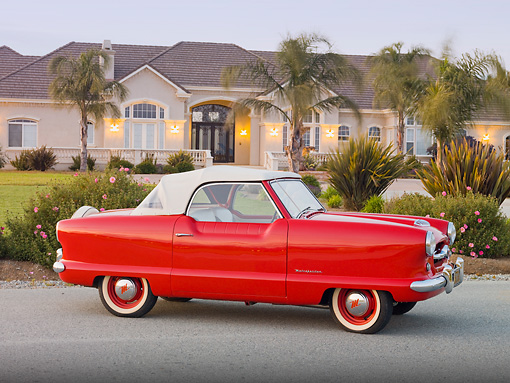 AUT 21 RK2643 01 © Kimball Stock 1955 Nash Metropolitan Convertible Red 3/4 Side View On Pavement By House