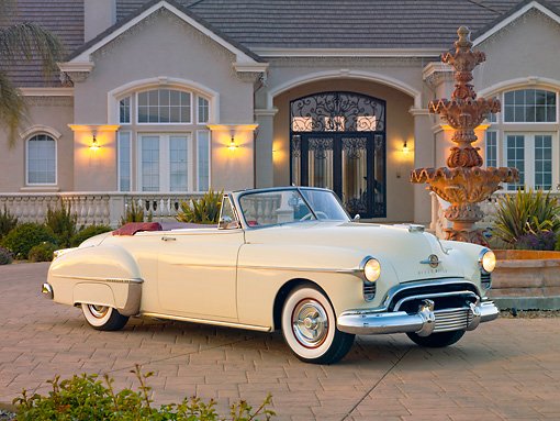 AUT 21 RK2649 01 © Kimball Stock 1950 Oldsmobile 88 Convertible White 3/4 Front View On Brick Road By House