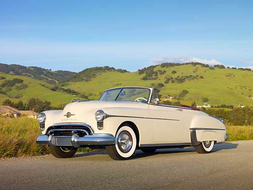 AUT 21 RK2651 01 © Kimball Stock 1950 Oldsmobile 88 Convertible White 3/4 Front View On Pavement By Grassy Hills