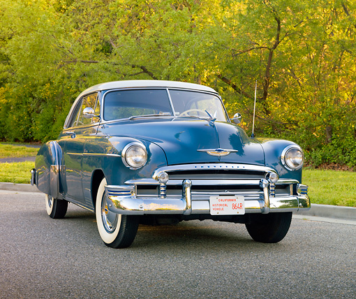AUT 21 RK2659 01 © Kimball Stock 1950 Chevrolet Bel Air Blue And Gray 3/4 Front View On Pavement By Trees