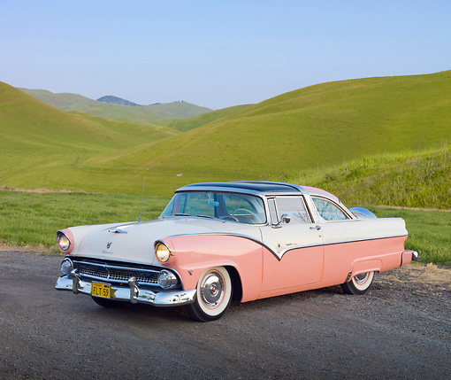 AUT 21 RK2666 01 © Kimball Stock 1955 Ford Crown Victoria Pink And White 3/4 Front View On Pavement By Trees And Grassy Hills