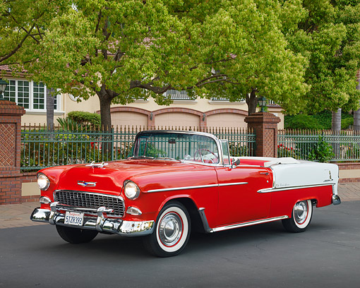 AUT 21 RK2711 01 © Kimball Stock 1955 Chevrolet Bel Air Convertible Red And White 3/4 Front View On Pavement By House