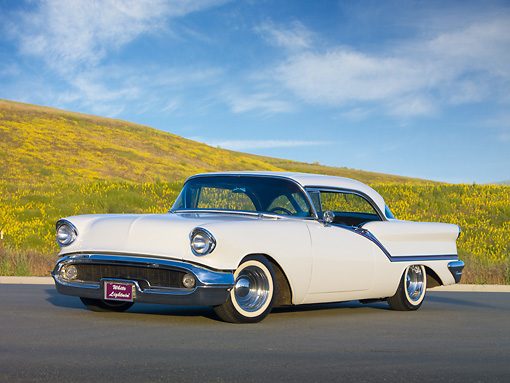 AUT 21 RK2714 01 © Kimball Stock 1957 Oldsmobile Super 88 Holiday Coupe White 3/4 Front View On Pavement By Wildflowers