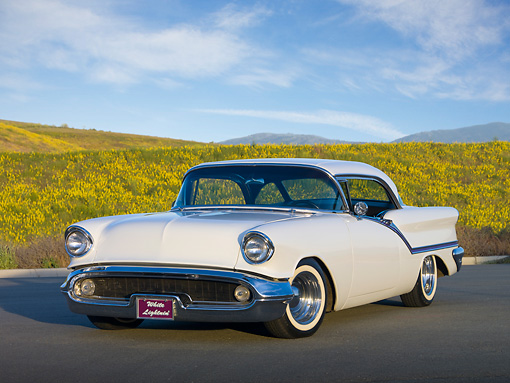 AUT 21 RK2715 01 © Kimball Stock 1957 Oldsmobile Super 88 Holiday Coupe White 3/4 Front View On Pavement By Wildflowers