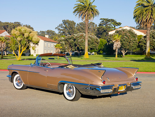 AUT 21 RK2726 01 © Kimball Stock 1958 Cadillac El Dorado Biarritz Bronze 3/4 Rear View On Pavement By Trees And Building