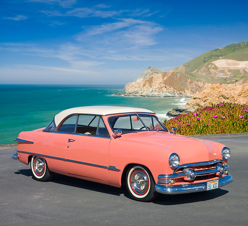 AUT 21 RK2812 01 © Kimball Stock 1951 Ford Victoria Coral And White 3/4 Front View On Pavement By Beach