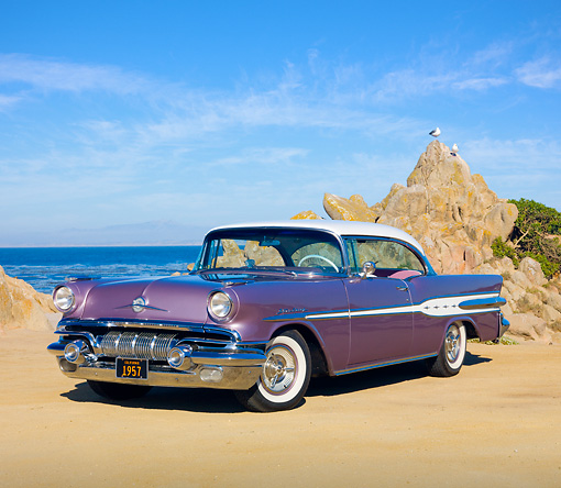 AUT 21 RK2819 01 © Kimball Stock 1957 Pontiac Star Chief Evening Orchid 3/4 Front View On Sand By Ocean