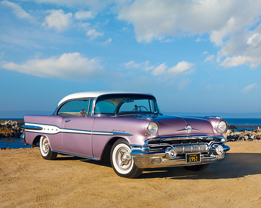 AUT 21 RK2822 01 © Kimball Stock 1957 Pontiac Star Chief Evening Orchid 3/4 Front View On Sand By Ocean