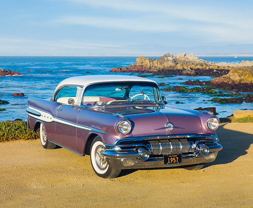 AUT 21 RK2824 01 © Kimball Stock 1957 Pontiac Star Chief Evening Orchid 3/4 Front View On Sand By Ocean