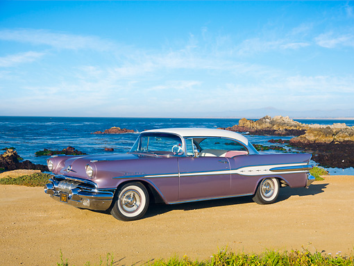 AUT 21 RK2826 01 © Kimball Stock 1957 Pontiac Star Chief Evening Orchid 3/4 Side View On Sand By Ocean