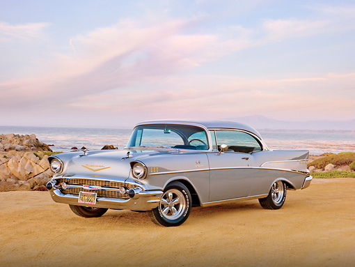 AUT 21 RK2829 01 © Kimball Stock 1957 Chevrolet Bel Air Silver 3/4 Front View On Sand By Ocean At Dusk