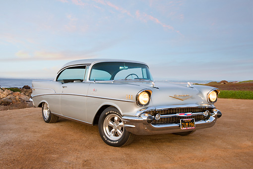 AUT 21 RK2830 01 © Kimball Stock 1957 Chevrolet Bel Air Silver 3/4 Front View On Sand By Ocean At Dusk