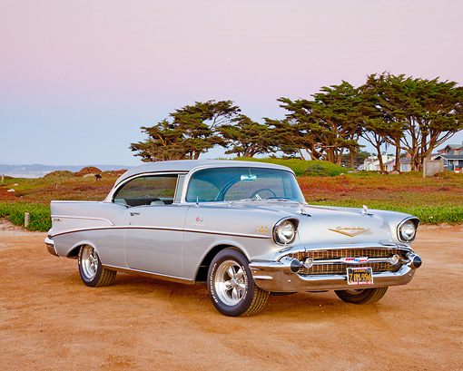 AUT 21 RK2832 01 © Kimball Stock 1957 Chevrolet Bel Air Silver 3/4 Front View On Sand By Trees And Houses At Dusk