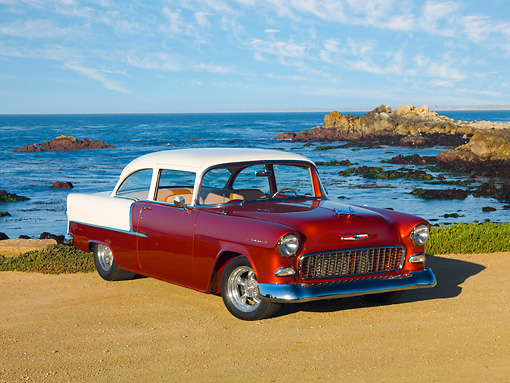 AUT 21 RK2835 01 © Kimball Stock 1955 Chevrolet 210 2-Door Sedan Orange And White 3/4 Front View On Sand By Ocean