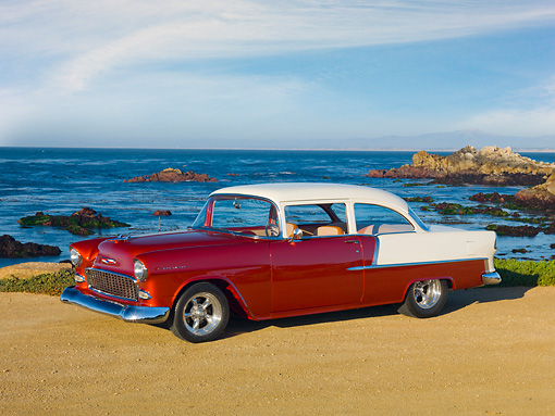AUT 21 RK2837 01 © Kimball Stock 1955 Chevrolet 210 2-Door Sedan Orange And White 3/4 Side View On Sand By Ocean