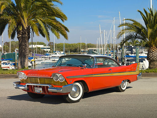 AUT 21 RK2845 01 © Kimball Stock 1957 Plymouth Fury Red And Gold 3/4 Front View On Pavement By Harbor And Palm Trees