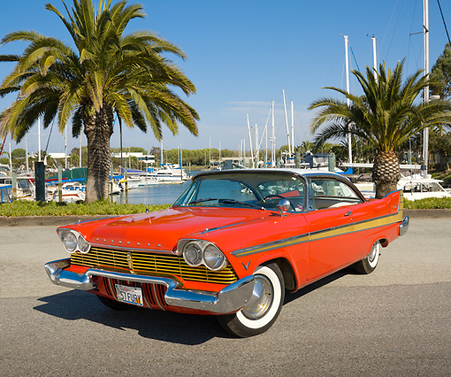 AUT 21 RK2848 01 © Kimball Stock 1957 Plymouth Fury Red And Gold 3/4 Front View On Pavement By Harbor And Palm Trees