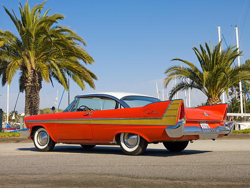 AUT 21 RK2849 01 © Kimball Stock 1957 Plymouth Fury Red And Gold 3/4 Rear View On Pavement By Harbor And Palm Trees