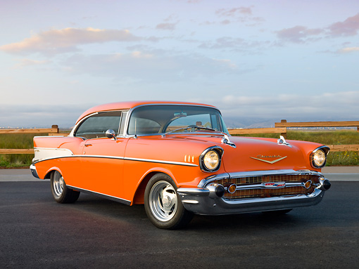 AUT 21 RK2866 01 © Kimball Stock 1957 Chevrolet Bel Air Orange 3/4 Front View On Pavement By Grass Field And Fence