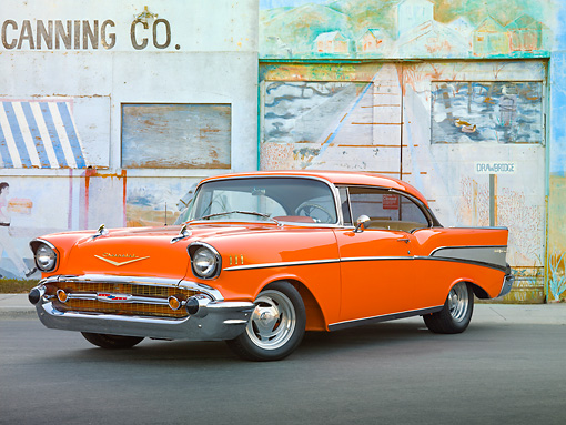 AUT 21 RK2867 01 © Kimball Stock 1957 Chevrolet Bel Air Orange 3/4 Front View On Pavement By Old Factory Building