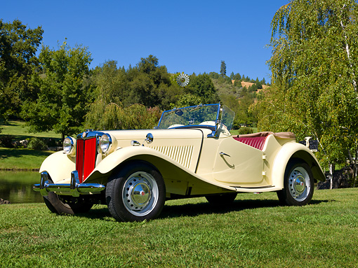 AUT 21 RK2877 01 © Kimball Stock 1953 MG TD Yellow 3/4 Front View On Grass By Pond