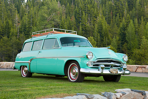 AUT 21 RK2878 01 © Kimball Stock 1954 Dodge Coronet Suburban Sea Green 3/4 Front View On Grass By Stones And Pine Trees
