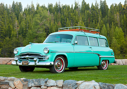 AUT 21 RK2879 01 © Kimball Stock 1954 Dodge Coronet Suburban Sea Green 3/4 Front View On Grass By Stones And Pine Trees