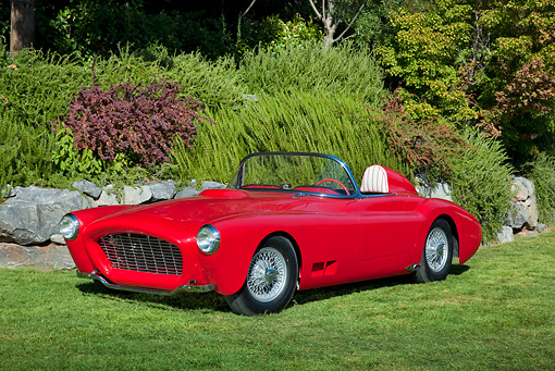 AUT 21 RK2880 01 © Kimball Stock 1958 Moore Roadster Red 3/4 Front View On Grass By Stones And Shrubs