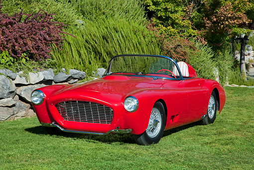 AUT 21 RK2881 01 © Kimball Stock 1958 Moore Roadster Red 3/4 Front View On Grass By Stones And Shrubs