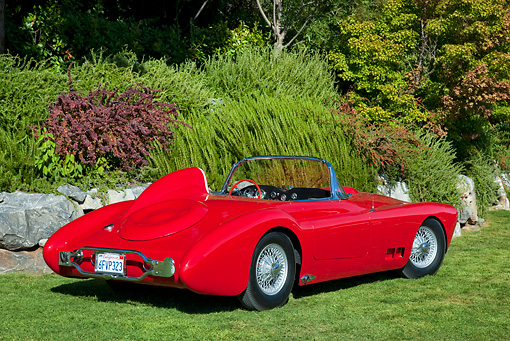AUT 21 RK2882 01 © Kimball Stock 1958 Moore Roadster Red 3/4 Rear View On Grass By Stones And Shrubs