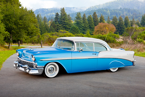 AUT 21 RK2929 01 © Kimball Stock 1956 Chevrolet Bel Air Blue And White 3/4 Side View On Pavement In Forest
