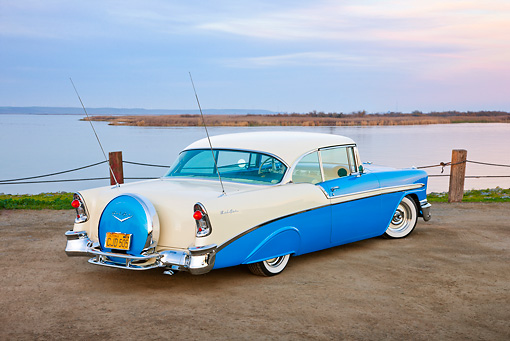 AUT 21 RK2930 01 © Kimball Stock 1956 Chevrolet Bel Air Blue And White 3/4 Rear View On Dirt Road By Water