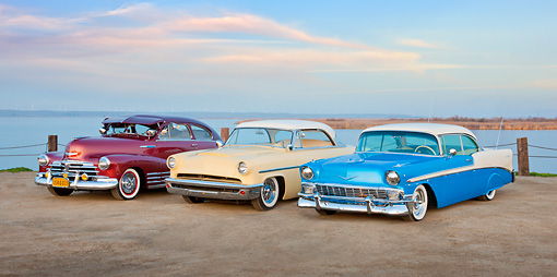AUT 21 RK2938 01 © Kimball Stock 1948 Chevrolet Fleetline Aerosedan Burgundy, 1953 Mercury Monterey Yellow And White And 1956 Chevrolet Bel Air Blue And White On Dirt Road By Water