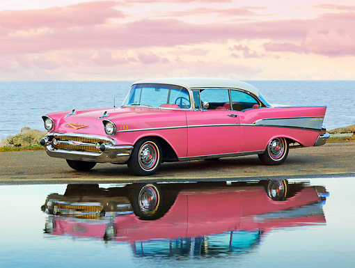 AUT 21 RK2967 01 © Kimball Stock 1957 Chevrolet Bel Air Pink 3/4 Side View On Pavement By Reflection In Water At Dusk