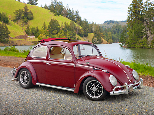 AUT 21 RK2980 01 © Kimball Stock 1959 Volkswagen Beetle Red 3/4 Side View On Gravel By Water And Grassy Hills