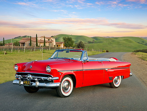 AUT 21 RK3009 01 © Kimball Stock 1954 Ford Sunliner Convertible Red 3/4 Front View On Road By Vineyard