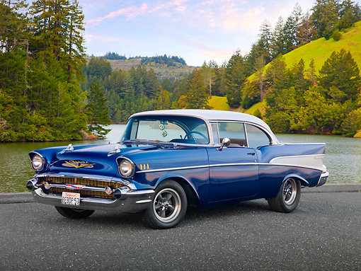 AUT 21 RK3016 01 © Kimball Stock 1957 Chevrolet Bel Air Blue And White 3/4 Front View On Pavement By Bay