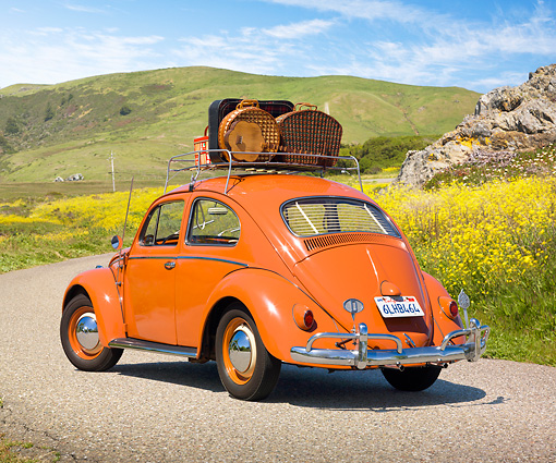 AUT 21 RK3031 01 © Kimball Stock 1958 VW Bug Sedan Coral Red With Luggage 3/4 Rear View On Pavement By Grassy Hills
