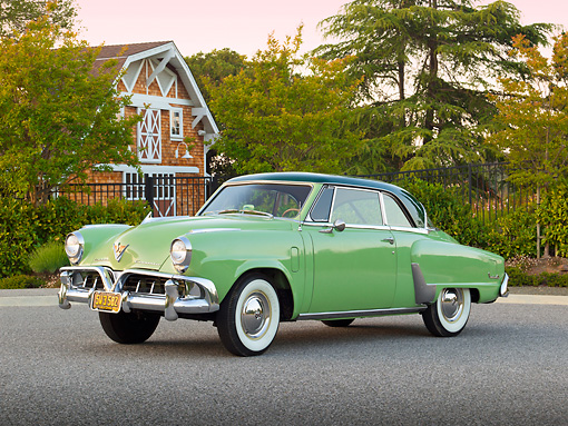 AUT 21 RK3048 01 © Kimball Stock 1952 Studebaker Commander Coupe Green 3/4 Front View On Pavement By House