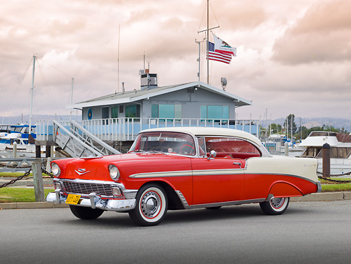 AUT 21 RK3063 01 © Kimball Stock 1956 Chevrolet Bel Air Matador Red And Dune Beige 3/4 Side View On Pavement By Harbor