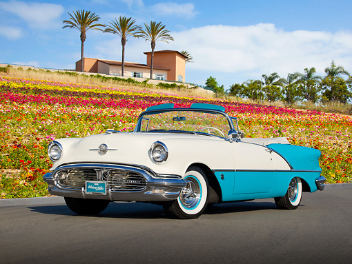 AUT 21 RK3087 01 © Kimball Stock 1956 Oldsmobile Super 88 Teal And White 3/4 Front View On Pavement By Flowers