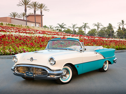 AUT 21 RK3093 01 © Kimball Stock 1956 Oldsmobile Super 88 Teal And White 3/4 Front View On Pavement By Flowers