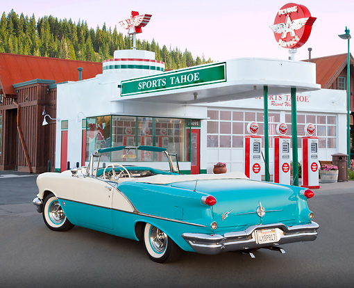 AUT 21 RK3100 01 © Kimball Stock 1956 Oldsmobile Super 88 Teal And White 3/4 Rear View On Pavement By Gas Station