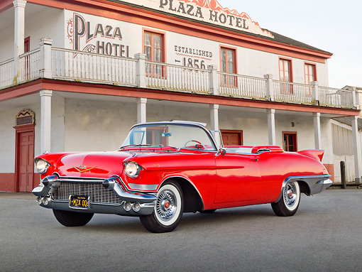 AUT 21 RK3185 01 © Kimball Stock 1957 Cadillac El Dorado Barritz Red 3/4 Front View On Pavement By Old Hotel